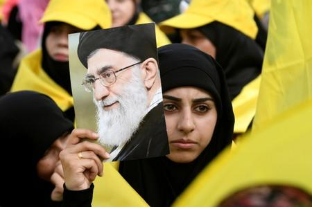 FILE PHOTO: A woman carries a picture of Iran's Supreme Leader Khamenei as she watches Lebanon's Hezbollah leader Nasrallah appear on a screen during a live broadcast to speak to his supporters at an event marking Resistance and Liberation Day in the Bekaa