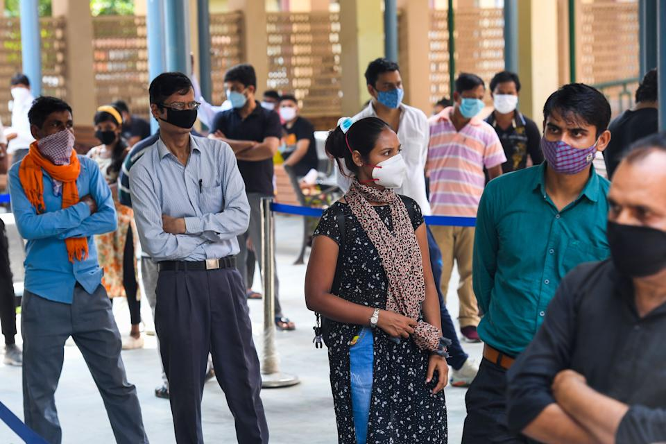 People wait in a queue for Rapid Antigen Test (RAT) for the coronavirus at an ayurvedic dispensary in a residential area in New Delhi on September 7, 2020. (Photo by PRAKASH SINGH/AFP via Getty Images)