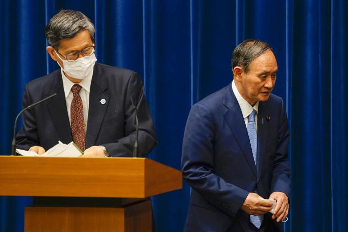 FILE - In this Aug. 17, 2021, file photo, Japanese Prime Minister Yoshihide Suga, right, walks past Shigeru Omi, chairman of the government's pandemic advisory panel, after a news conference at prime minister's official residence in Tokyo. Suga announced on Aug. 17, 2021, a decision to expand and extend a state-of-emergency covering Tokyo and other areas until at least mid-September, although most of the restrictions aren't legally enforceable. (Kimimasa Mayama/Pool via AP, File)