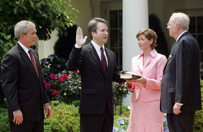 FILE - In this June 1, 2006 file photo, from left to right, President Bush, watches the swearing-in of Brett Kavanaugh as Judge for the U.S. Court of Appeals for the District of Columbia by U.S. Supreme Court Associate Justice Anthony M. Kennedy, far right, during a ceremony in the Rose Garden of the White House, in Washington. Holding the Bible is Kavanaugh's wife Ashley Kavanaugh. Kavanaugh has been a conservative team player, and the Supreme Court nominee has stepped up to make a play at key moments in politics, government and the law dating to the Bill Clinton era. (AP Photo/Pablo Martinez Monsivais, File)