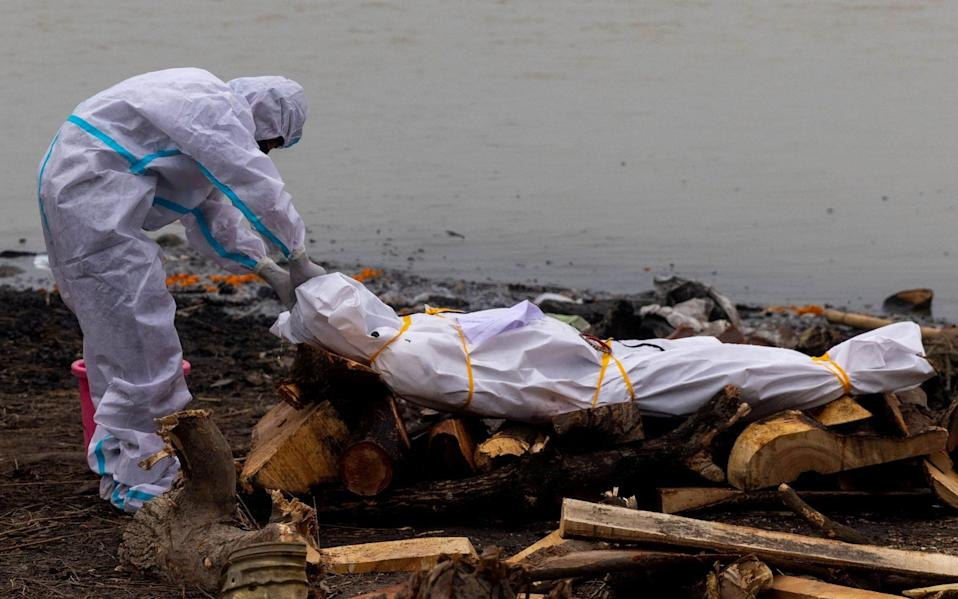 A man wearing a protective suit touches the body of his relative, who died from Covid-19 before his cremation on the banks of the river Ganges at Garhmukteshwar - DANISH SIDDIQUI / REUTERS