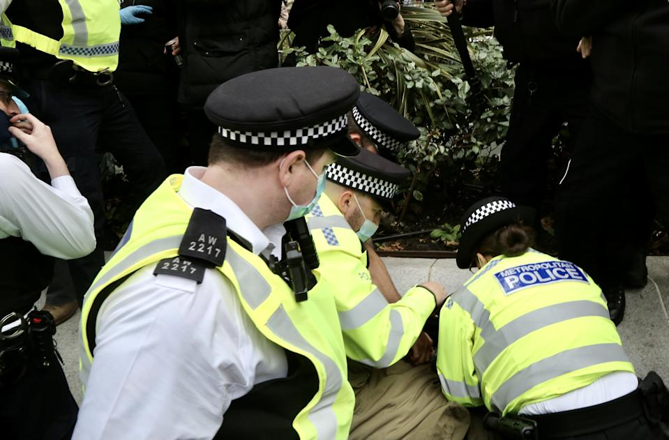 LONDON, UNITED KINGDOM - OCTOBER 17: Police officers take into custody some protesters as members of StandUpX stage a protest against coronavirus (Covid-19) measures and vaccine despite social gatherings of more than six people are not be allowed within Covid-19 measures in London, United Kingdom on October 17, 2020. (Photo by Hasan Esen/Anadolu Agency via Getty Images)