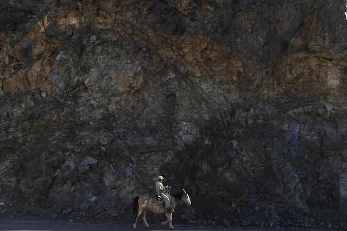 In this May 23, 2013 photo, Juan Guerrero rides past a wall of rock as he rides into El Corral, a small town of about 200 inhabitants, mostly from the Diaguita ethnic group, near the facilities of Barrick Gold Corp's Pascua-Lama project in northern Chile. The Diaguitas live in the foothills of the Andes, where for as long as anyone can remember they've drunk straight from the glacier-fed river that irrigates their orchards and vineyards with clean water. But since Barrick gold mine project moved in, the residents claim the river levels have dropped and some complain of cancerous growths and aching stomachs. (AP Photo/Jorge Saenz)