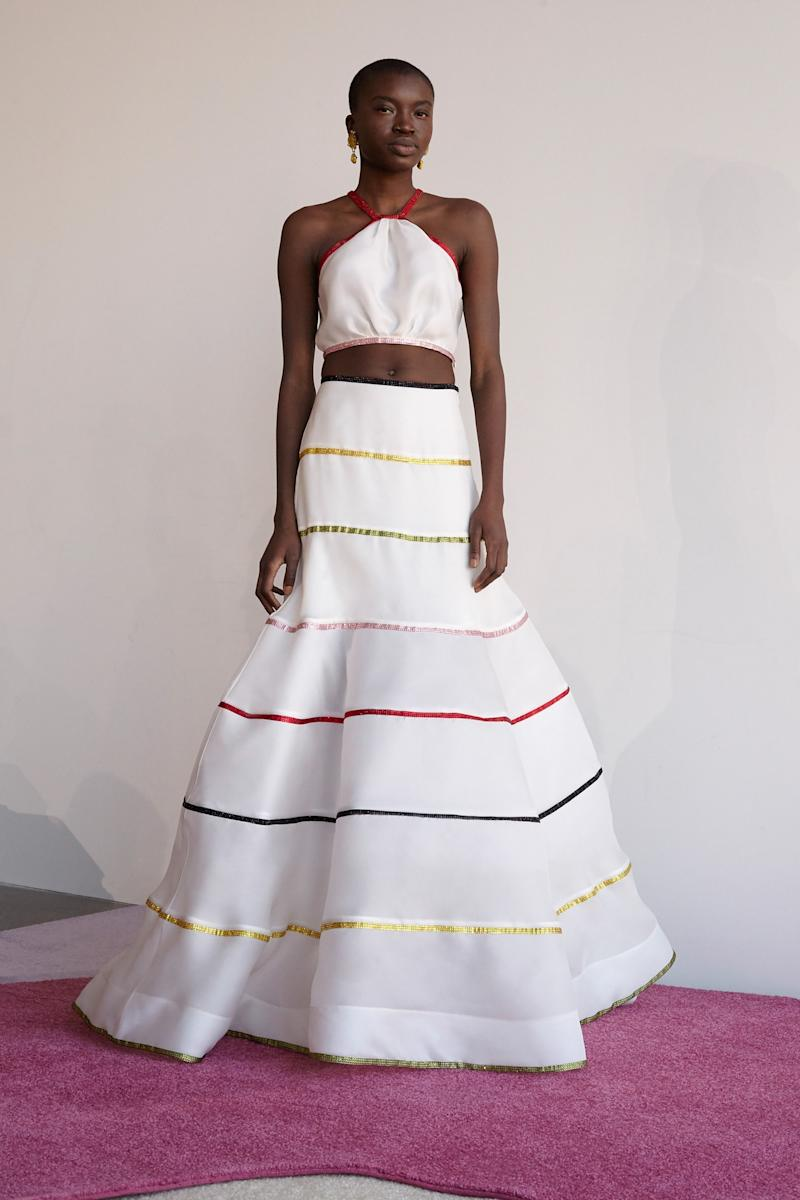 Image result for Rosie Assoulin Who says you can't wear a crop top on your wedding day? Certainly not Assoulin, who paired a midriff-baring halter with a maxi skirt with rainbow-stripe trim—a convincing combination for the bride who dreams of tying the knot barefoot on a white-sand beach.