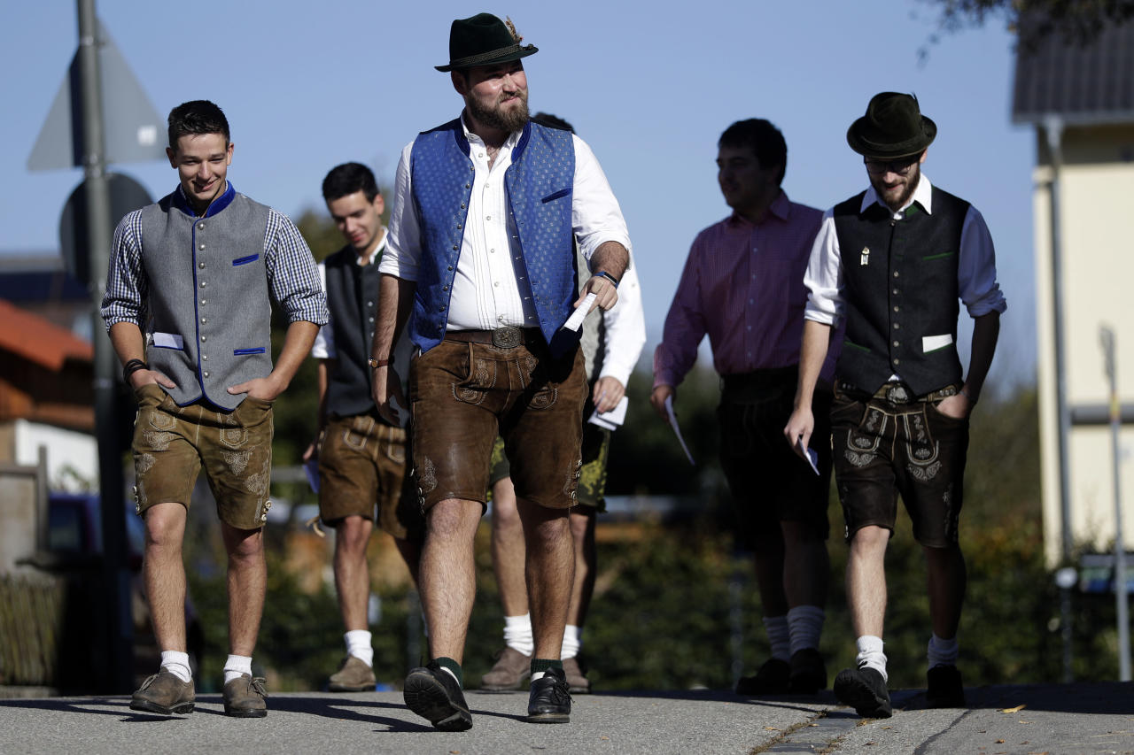 Young men in traditional Bavarian clothes arrive at a polling station for the Bavarian state elections in Maisach, southern Germany, Sunday, Oct. 14, 2018. (AP Photo/Matthias Schrader)
