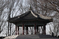 A man wearing a face mask walks past near a pavilion which is taped off for the social distancing measures and a precaution against the coronavirus at a park in Seoul, South Korea, Thursday, Dec. 24, 2020. (AP Photo/Lee Jin-man)