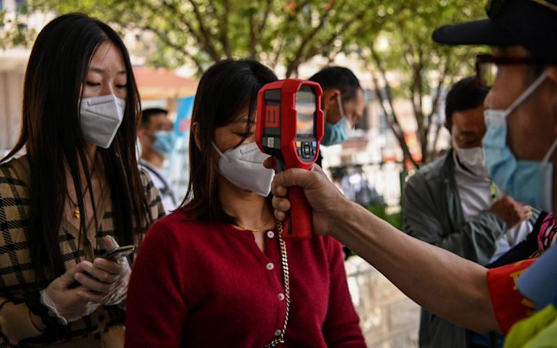 A worker wearing a face mask checks passengers body temperatures and a health code on their phones before they take a taxi after arriving at Hankou railway station in Wuhan, Hubei Province - AFP