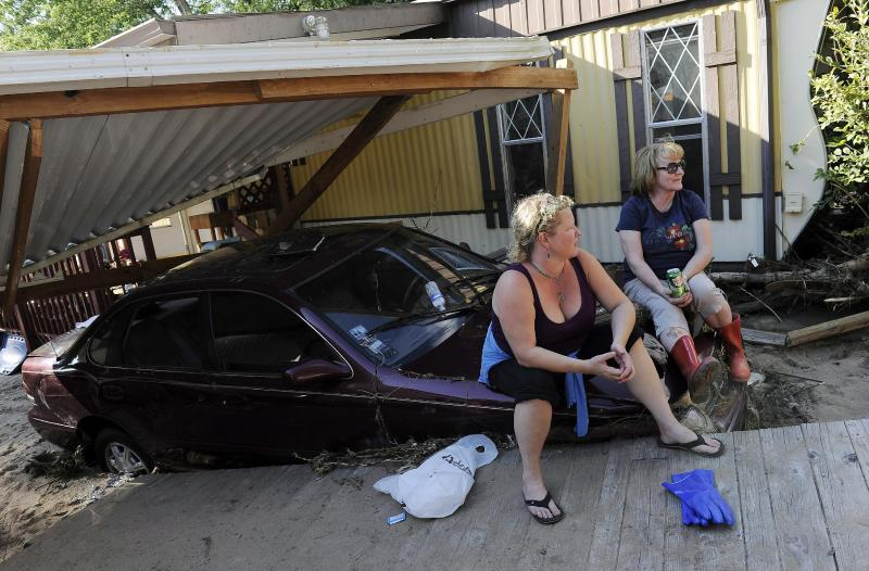 Jenna Brink, left, takes a break while clearing belongings from her flood-damaged trailer with her mother, Christine Brink, at the River Bend Mobile Home Park in Lyons, Colo., on Thursday, Sept. 19, 2013. Hundreds of evacuees were allowed past National Guard roadblocks Thursday to find a scene of tangled power lines, downed utility poles, and mud-caked homes and vehicles. (AP Photo/Chris Schneider)