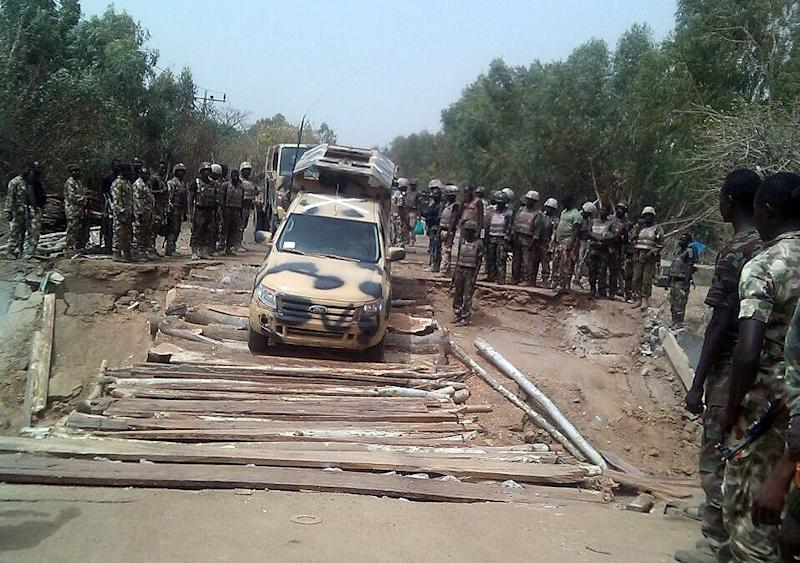A photo taken on March 15, 2015 by the Nigerian Army press service shows troops crossing the Kaffin-Hausa bridge earlier destroyed by terrorists and reconstructed by military engineers at Damasak in Borno State (AFP Photo/)