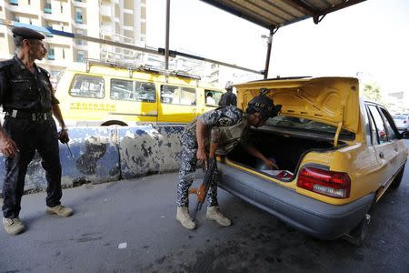 A member of Iraqi security forces searches the trunk of a vehicle at a checkpoint, as security increases in Baghdad