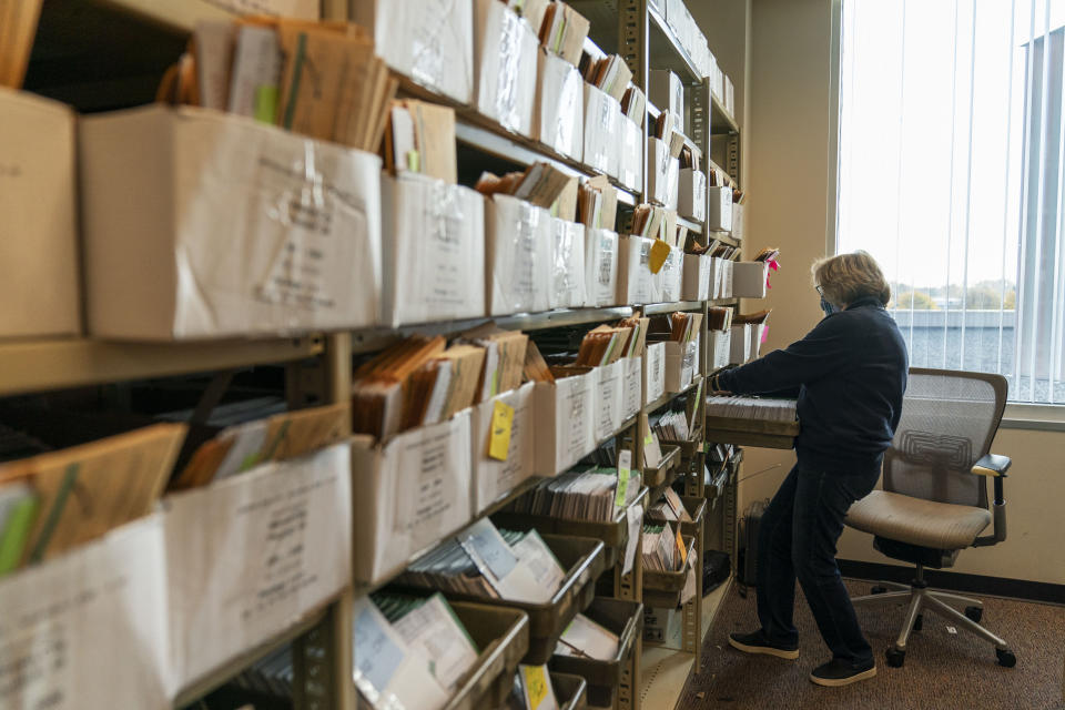 Election worker Mary Pluszczynsky organizes absentee ballots ahead of Tuesday's general election at the city clerk office in Warren, Mich., Wednesday, Oct. 28, 2020. (AP Photo/David Goldman)