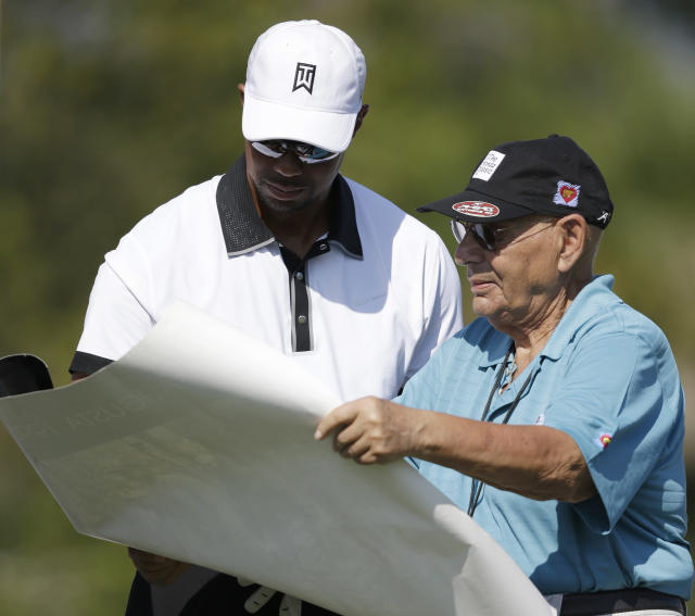 Golfer Tiger Woods, left, autographs a poster for marshall Frank Buterwaiser during the Pro-Am round of the Honda Classic golf tournament, Wednesday, Feb. 26, 2014 in Palm Beach Gardens, Fla. (AP Photo/Wilfredo Lee)