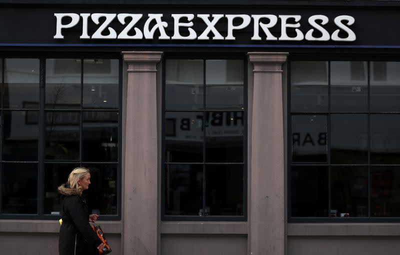 A woman walks past a Pizza Express restaurant in London