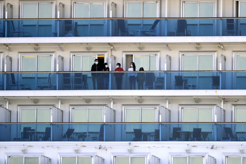 Passengers stand on the balcony of the quarantined Diamond Princess cruise ship anchored at a port in Yokohama, near Tokyo, Friday, Feb. 21, 2020. Passengers tested negative for COVID-19 started disembarking since Wednesday. (AP Photo/Eugene Hoshiko)