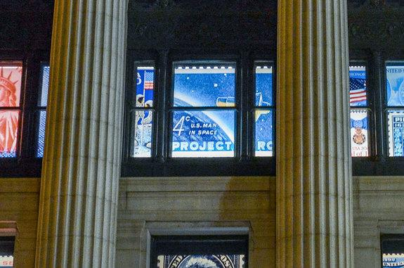 """Enlarged reproductions of the """"20th Anniversary Moon Landing"""" and """"Project Mercury"""" stamps adorn the windows of the William H. Gross Stamp Gallery at the National Postal Museum."""