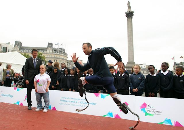 LONDON, ENGLAND - SEPTEMBER 8: Oscar Pistorius shows off his skills as Chairman of LOCOG Lord Coe and Ellie Simmonds look on during the International Paralympic Day at Trafalgar Square on September 8, 2011 in London, England. The day marks the start of Paralympic tickets going on sale on September 9, 2011. (Photo by Jan Kruger/Getty Images)