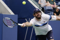 Reilly Opelka, of the United States, returns a shot against Lloyd Harris, of South Africa, during the fourth round of the US Open tennis championships, Monday, Sept. 6, 2021, in New York. (AP Photo/Elise Amendola)