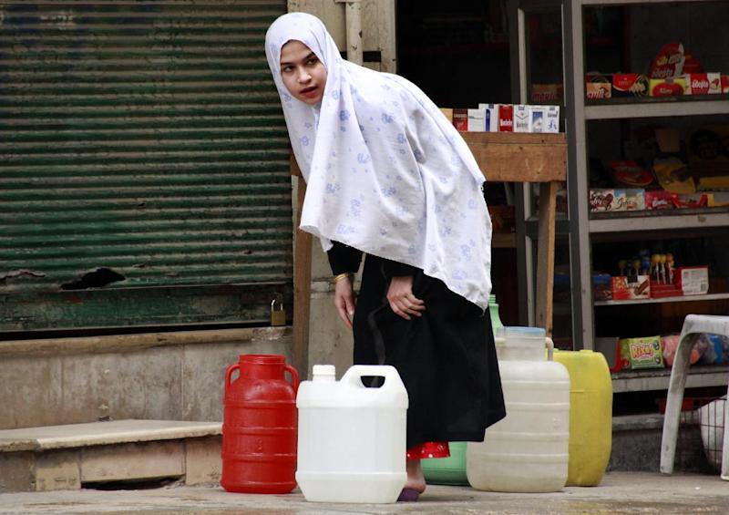 A Syrian girl prepares to carry jerrycans filled with water in Aleppo on May 8, 2014 (AFP Photo/Baraa al-Halabi)