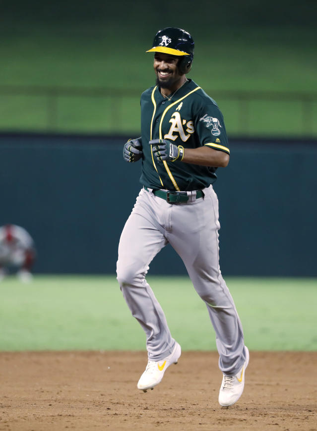 Oakland Athletics' Marcus Semien smiles as he runs the bases after hitting a two-run home run against the Texas Rangers during the ninth inning of a baseball game in Arlington, Texas, Friday, Sept. 13, 2019. (AP Photo/Tony Gutierrez)