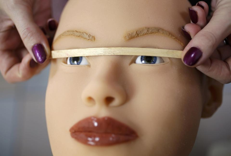 Raphaela, an employee at the Dreamdoll company, checks eye alignment on a silicone dream doll in their workshop in Duppigheim near Strasbourg, December 2, 2014. The realistic silicone sex dolls can be ordered from a catalogue based on four hair and eye color models for a base price of 5,500 euros ($6,150). The dolls weigh around 40 kilos due to a lightweight aluminum structure and take a week to construct. The company of three employees produces some one hundred custom-made silicone sex dolls a year, mainly for European customers. Picture taken December 2, 2014. REUTERS/Vincent Kessler (FRANCE - Tags: SOCIETY BUSINESS)