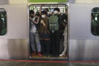 Commuters pack into a train car in Tokyo Friday, Oct. 8, 2021, the morning after a strongearthquake has shaken the Tokyo area Thursday night, temporarily halting trains and subways. (AP Photo/Kiichiro Sato)