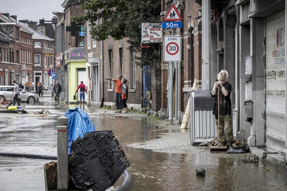 A man sweeps water and mud out of his house on a residential street after flooding in Angleur, Province of Liege, Belgium, Friday July 16, 2021. Severe flooding in Germany and Belgium has turned streams and streets into raging torrents that have swept away cars and caused houses to collapse. (AP Photo/Valentin Bianchi)
