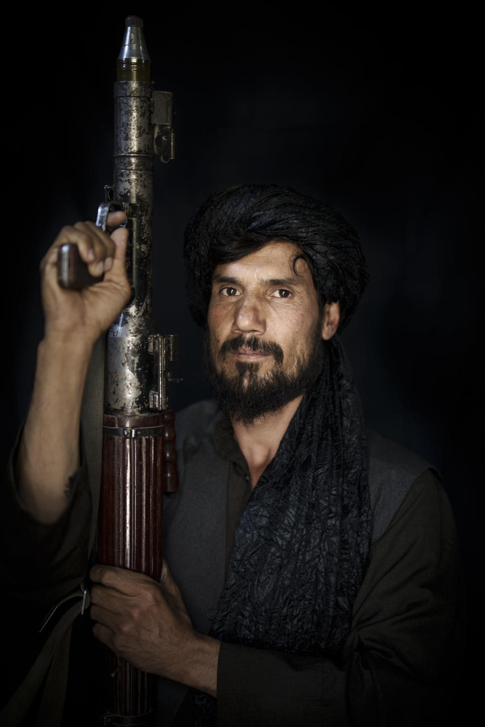 Taliban fighter Mohammad Adel, 43, poses for a photo holding a rocket-propelled grenade, RPG, at a police station in Kabul, Afghanistan, Thursday, Sept. 16, 2021. Adel is from a village near Kabul and has been a Taliban for more than 20 years. He says he went into hiding after US forces entered Afghanistan. (AP Photo/Felipe Dana)