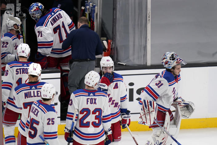New York Rangers goaltender Keith Kinkaid (71) heads to the locker room after an apparent injury as goaltender Igor Shesterkin (31) skates to the crease during the third period of an NHL hockey game against the Boston Bruins, Saturday, May 8, 2021, in Boston. (AP Photo/Charles Krupa)