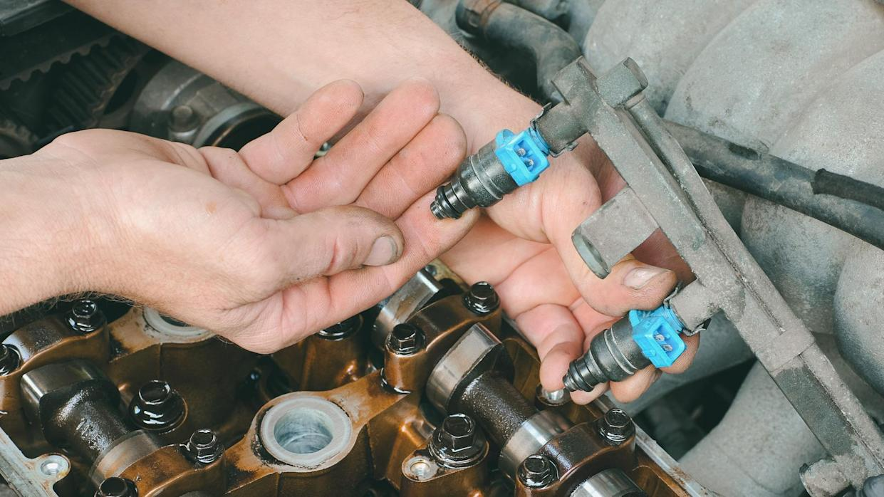 Car mechanic fixing fuel injector at  two camshaft gasoline engine.