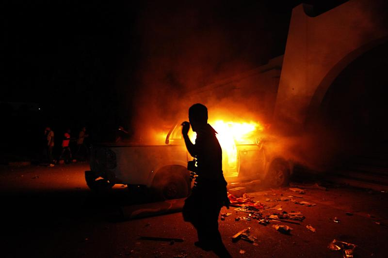 A Libyan civilian watches one of Ansar al-Shariah Brigades cars on fire, after hundreds of Libyans, Libyan Military, and Police raided the Brigades base, in Benghazi, Libya, Friday, Sept. 21, 2012. The recent attack that killed the U.S. ambassador and three other Americans has sparked a backlash among frustrated Libyans against the heavily armed gunmen, including Islamic extremists, who run rampant in their cities. More than 10,000 people poured into a main boulevard of Benghazi, demanding that militias disband as the public tries to do what Libya's weak central government has been unable to. (AP Photo/Mohammad Hannon)