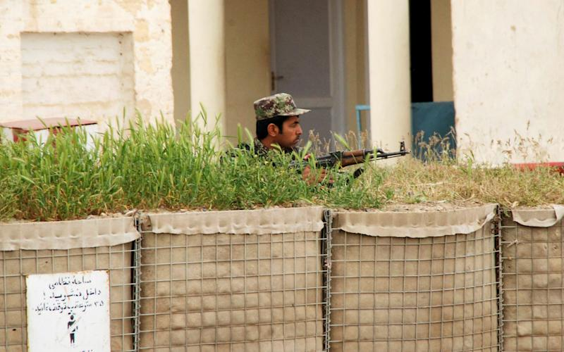 An Afghan security official stands guard near the site where several militants in Afghan army uniform targeted an army base during Friday prayers - Credit: EPA