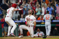 Philadelphia Phillies' Bryce Harper (3) and Andrew Knapp (5) celebrate after Harper scored the game-winning run on a two-run triple by J.T. Realmuto during the 10th inning of an interleague baseball game against the Baltimore Orioles, Tuesday, Sept. 21, 2021, in Philadelphia. (AP Photo/Matt Slocum)