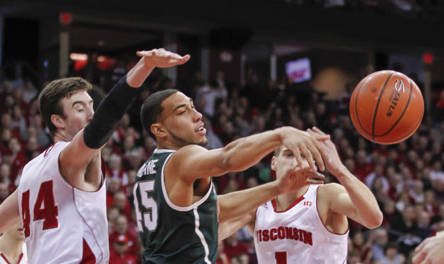 Michigan State's Denzel Valentine, center, passes against Wisconin's Frank Kaminsky, left, and Ben Brust during the first half of an NCAA college basketball game on Sunday, Feb. 9, 2014, in Madison, Wis. (AP Photo/Andy Manis)
