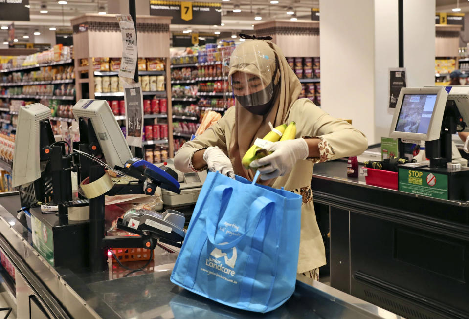 A staff wearing protective gear as a precaution against the new coronavirus outbreak checks out a customer at a supermarket in Jakarta, Indonesia, Wednesday, July 1, 2020. The government of Indonesia's capital region is extending the first transition phase from large-scale social restrictions in Jakarta as the number of new confirmed coronavirus cases continues to rise. (AP Photo/Tatan Syuflana)