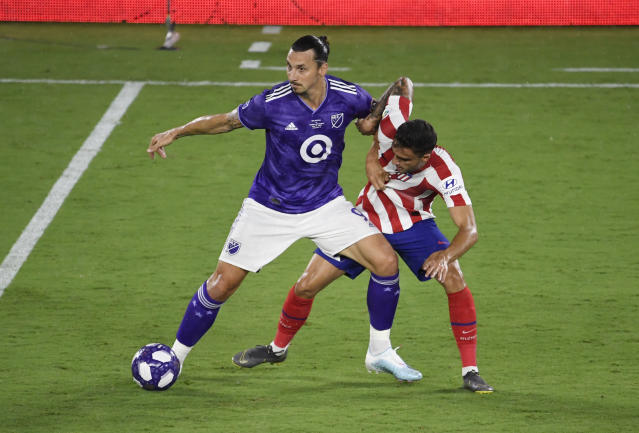 Zlatan Ibrahimovic (9) holds off Atletico Madrid's Carlos Isaac during the MLS All-Star Game on Wednesday in Orlando, Fla. (Getty)