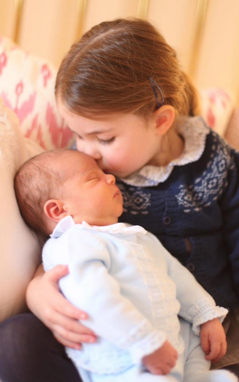 Princess Charlotte gives her baby brother Prince Louis a tender kiss - PA