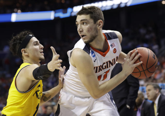 Virginia's Ty Jerome, right, is guarded by UMBC's K.J. Maura during the first half of a first-round game in the NCAA men's college basketball tournament in Charlotte, N.C., Friday, March 16, 2018. (AP Photo/Gerry Broome)