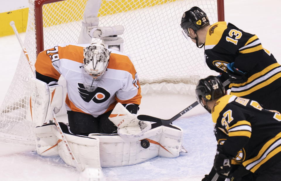 Philadelphia Flyers goaltender Carter Hart (79) makes a save as Boston Bruins centers Charlie Coyle (13) and Patrice Bergeron (37) close in during third-period NHL hockey playoff action in Toronto, Sunday, Aug. 2, 2020. (Frank Gunn/The Canadian Press via AP)