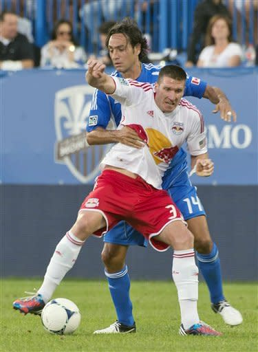 New York Red Bulls' Kenny Cooper, front, tangles with Montreal Impact's Alessandro Nesta during the first half of an MLS soccer game Saturday, July 28, 2012, in Montreal. (AP Photo/The Canadian Press, Peter McCabe)