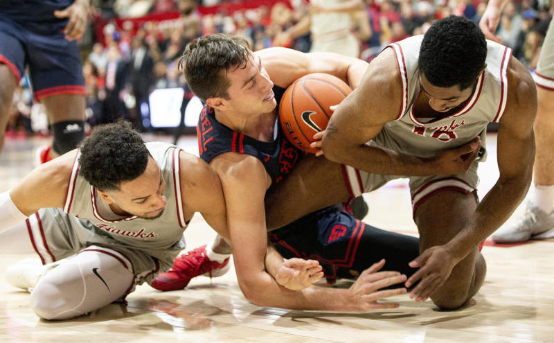 Dayton forward Ryan Mikesell, center, fights for the ball with Saint Joseph's forward Lorenzo Edwards, left, and guard Rahmir Moore, right, during the first half of an NCAA college basketball game, Sunday, Jan. 5, 2020, in Philadelphia. (AP Photo/Laurence Kesterson)