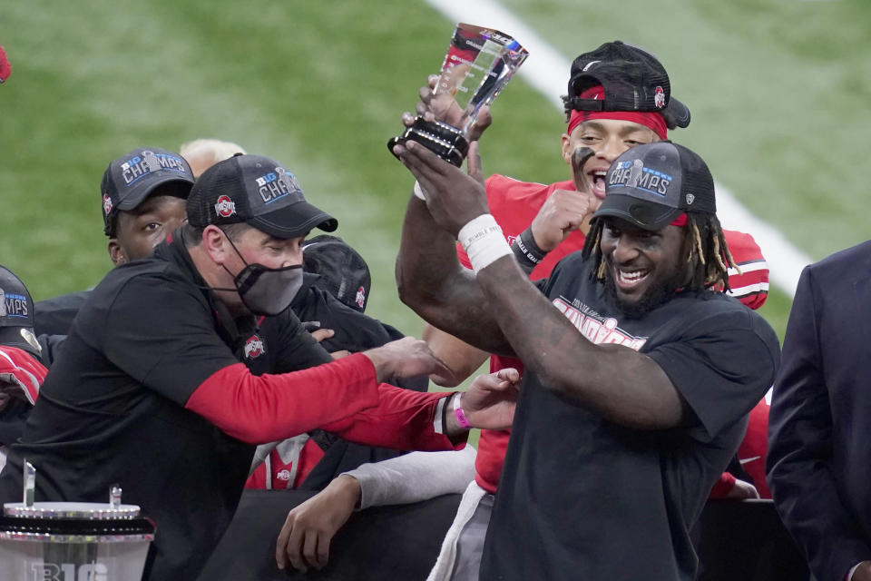 Ohio State running back Trey Sermon, right, is congratulated by head coach Ryan Day, left, after being named most valuable player following the Big Ten championship NCAA college football game, Saturday, Dec. 19, 2020, in Indianapolis. Ohio State defeated Northwestern 22-10. (AP Photo/Darron Cummings)