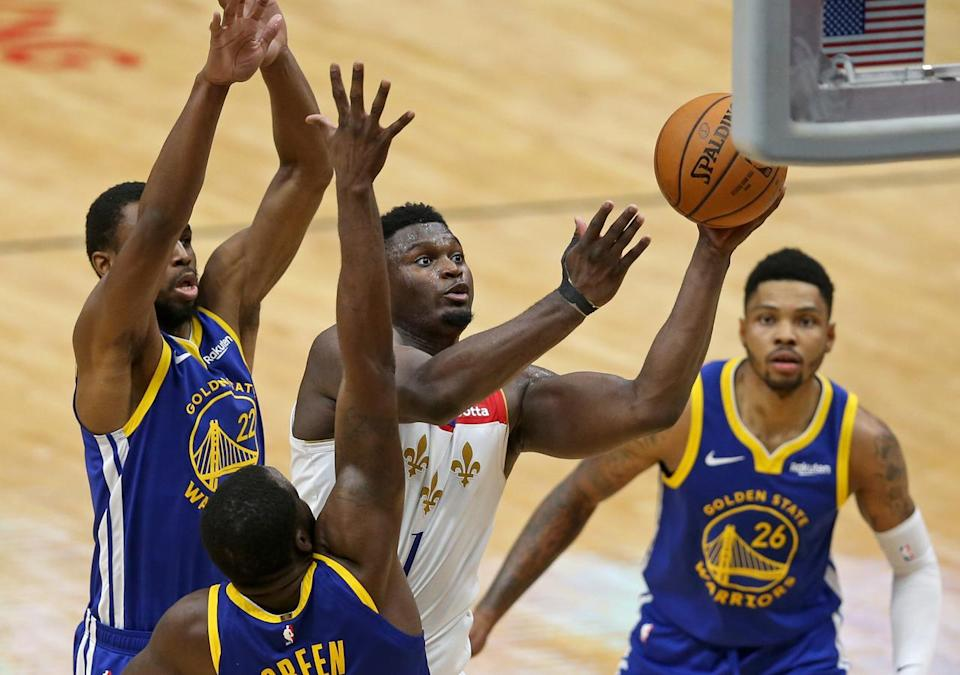 Zion Williamson attacks the rim surrounded by Warriors