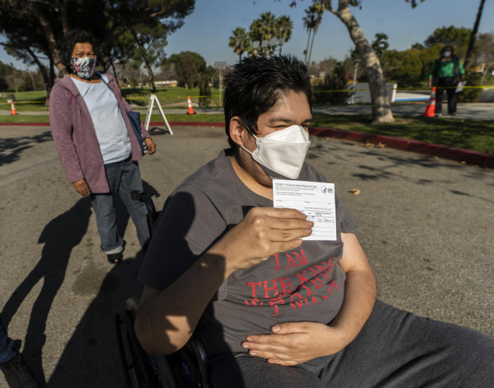 Cancer survivor, Joel Flores, who has Autism Spectrum Disorder, holds up his vaccination card after being able to receive his first vaccine shot at the COVID-19 vaccination site at the East Los Angeles Civic Center in Los Angeles on Thursday, March 4, 2021. His mother, Emilia del Carmen Flores, left, originally from El Salvador, also got the vaccine. California will begin setting aside 40% of all vaccine doses for the state's most vulnerable neighborhoods in an effort to inoculate people most at risk from the coronavirus more quickly. (AP Photo/Damian Dovarganes)