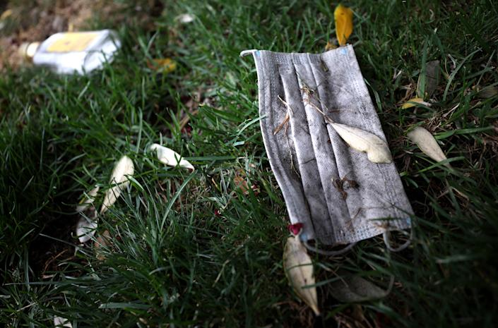 A discarded surgical mask sits on grass