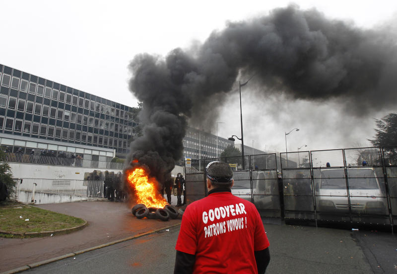 "FILE - In this March 7, 2013 file photo, a Goodyear worker wearing a tee shirt reading ""Goodyear, thug bosses"" stands near burning tires, as police officers form a line during a demonstration against layoffs, at the Goodyear headquarters in Rueil Malmaison, west of Paris. Tensions - and even confrontation - between unions and management have long been the norm in France. Strikes and protests have periodically paralyzed the country. (AP Photo/Remy de la Mauviniere, File)"