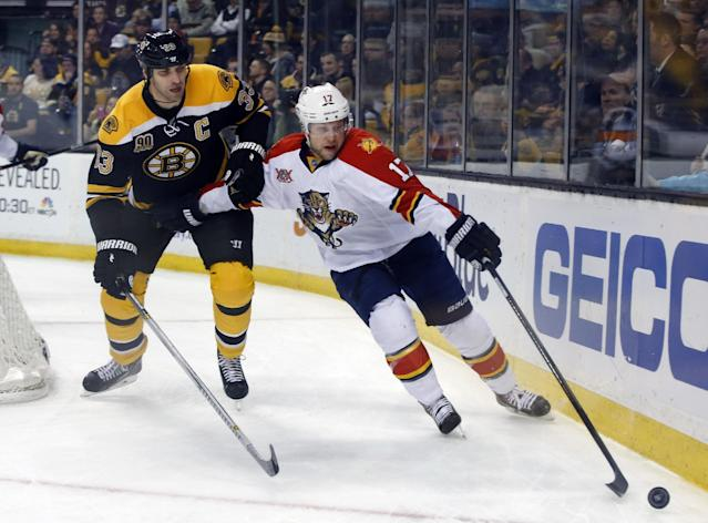 Boston Bruins defenseman Zdeno Chara (33) tries to keep Florida Panthers center Jesse Winchester (17) from the puck during the first period of an NHL hockey game in Boston, Tuesday, Jan. 28, 2014. (AP Photo/Elise Amendola)