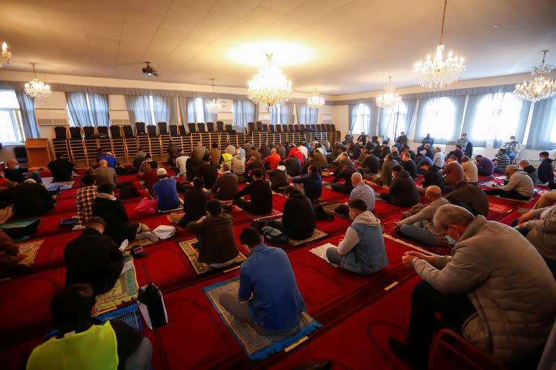 Muslims pray for victims of a gun attack during their Friday prayer in a mosque in Vienna