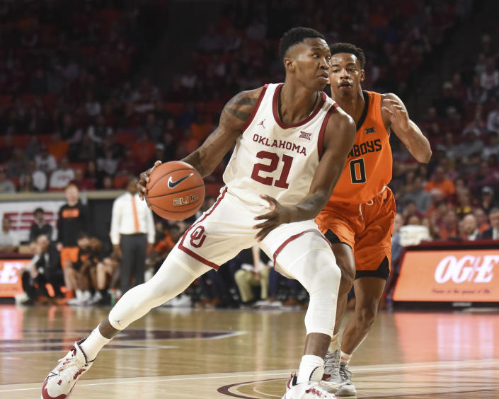 Oklahoma forward Kristian Doolittle (21) pushes past Oklahoma St guard Avery Anderson III (0) during the second half of an NCAA college basketball game in Norman, Okla., Saturday, Feb. 1, 2020. (AP Photo/Kyle Phillips)
