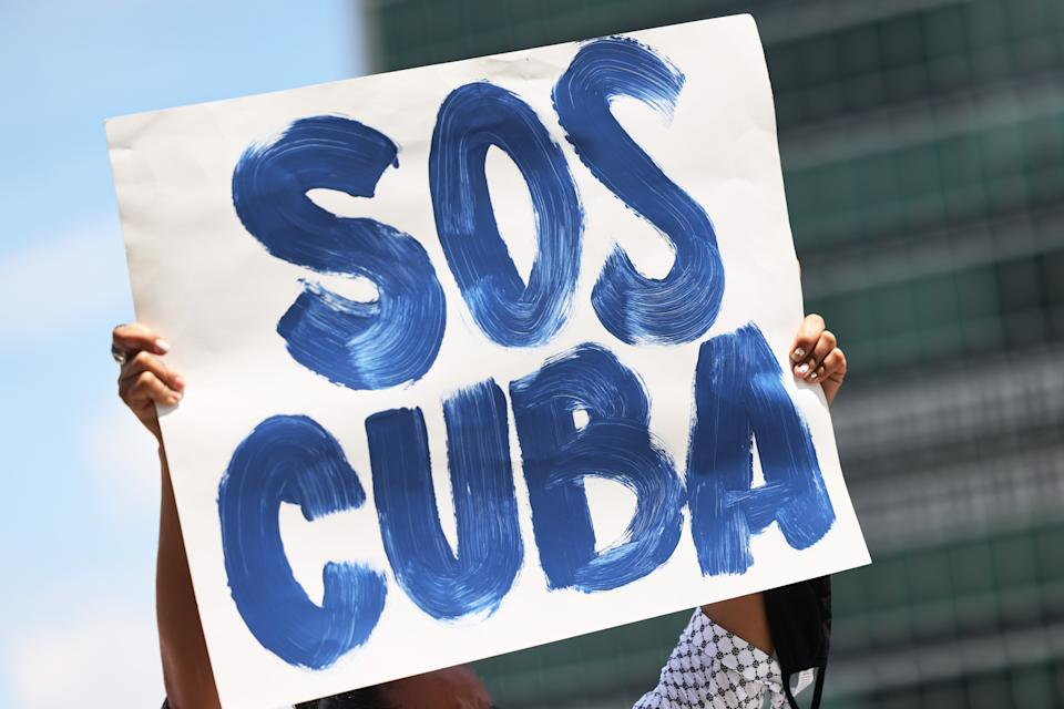 NEW YORK, NEW YORK - JULY 14: A person holds up a protest sign as people gather calling for help for Cuban protestors on the island in front of the United Nations on July 14, 2021in New York City. A small group of people gathered in front of the United Nations in support of the people of Cuba who have been protesting against the communist regime due to food shortage and worsening economic crisis that has been exasperated by the coronavirus (COVID-19) pandemic. The protest on the island has been the largest anti-government protest in decades. (Photo by Michael M. Santiago/Getty Images)