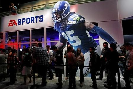 "People wait in-line under ""Madden NFL 15"" billboard with an image of NFL player Sherman at the Electronic Arts booth during the 2014 Electronic Entertainment Expo, known as E3, in Los Angeles"